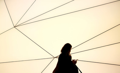 A woman looks at her phone in front of the Samsung network stand at the Mobile World Congress in Barcelona
