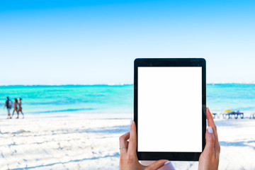 Blank empty tablet computer in the hands of girl on the beach