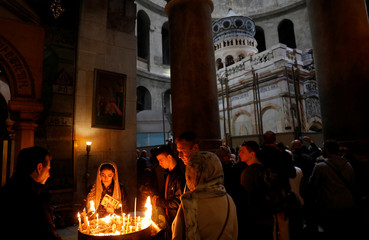 Worshippers light candles as the newly restored Edicule is seen in the background at the Church of the Holy Sepulchre in Jerusalem's Old City