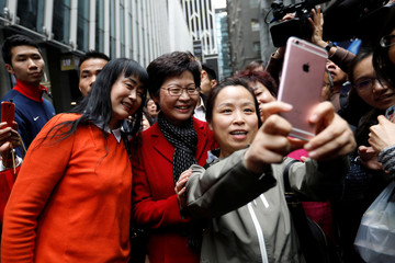 People take selfies with Carrie Lam, chief executive-elect, a day after she was elected in Hong Kong