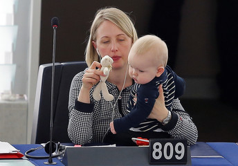 Swedish MEP Guteland holds her baby as she takes part in a voting session at the European Parliament in Strasbourg