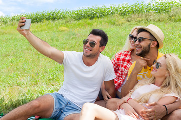 Friends taking selfie photo smart phone picnic countryside young people group sitting blanket outdoor green grass two couple summer sunny day