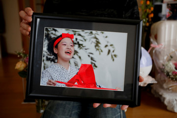 Go Kasai, father of Rima Kasai who killed herself, poses with Kasai's picture at his house during an interview with Reuters in Fujisaki