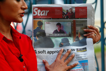 A journalist holds up a newspaper showing a photo of a man who claims to be the son of Kim Jong Nam outside the North Korean embassy in Kuala Lumpur