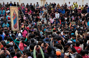 People take pictures of the Candelaria virgin image during the annual brass band festival to kick off pre-Carnival festivities in Oruro