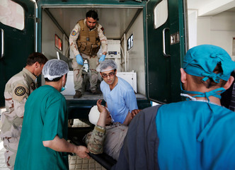 Men carry an injured Afghan security force to a hospital after attack in Kabul, Afghanistan