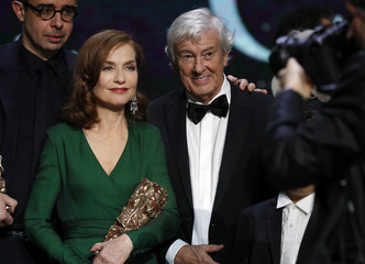 "Actress Isabelle Huppert, Best Actress Award for her role in the film ""Elle"", poses with director Paul Verhoeven, Best Film Award for his film ""Elle"", at the end of the 42nd Cesar Awards ceremony in Paris"