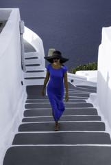 Lady in blue long dress walks on steps in Oia village, Santorini island, Greece