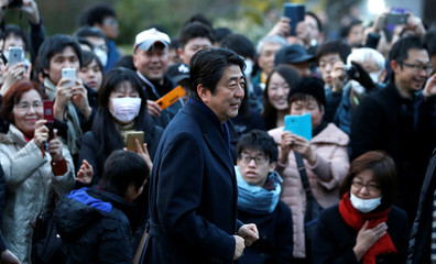 People take pictures of Japan's PM Abe as he attends a Friday night concert outside a museum in Tokyo