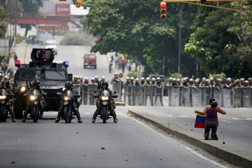 A demonstrator knees in front of riot police during a rally against Venezuela's President Maduro in Caracas