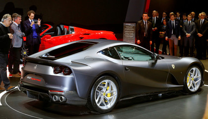 Fiat Chrysler CEO Marchionne stands beside as Fiat Chrysler Chairman Elkann takes a picture of the new Ferrari 812 Superfast during the 87th International Motor Show at Palexpo in Geneva