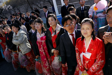 People react as a vehicle carrying foreign reporters passes towards the newly constructed residential complex before its opening in Ryomyong street in Pyongyang