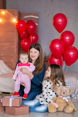 beautiful young mother and daughter in dresses with wreathes on their hads with colorful baloons in photo studio