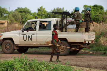 A girl walk past Cameroonian United Nations peacekeeping soldiers on guard in the village of Bambara