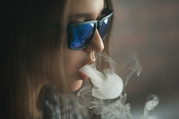 Vape. Young handsome white girl in sunglasses is admiting puffs of steam from the electronic cigarette. Vaping. Teenager.