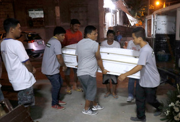 Residents carry the coffin of an alleged drug dealer,  whom police said killed in a buy bust drug operation in Malolos, Bulacan