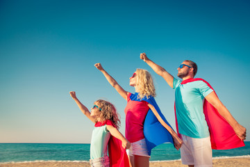 Family of superheroes on the beach. Summer vacation concept