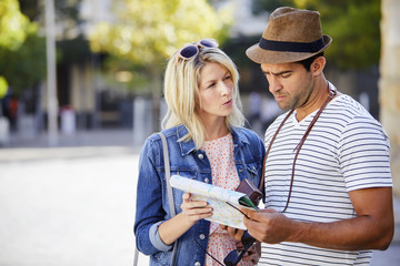 Map reading couple in city, frowning