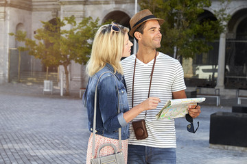 Tourist couple on city break with map, smiling