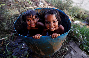 Girls bath inside a drum on a hot summer day at a field in New Delhi
