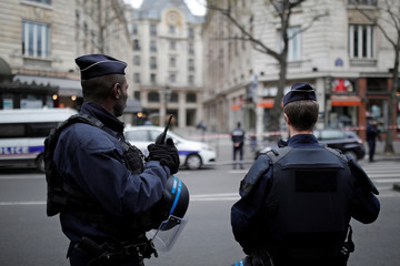 French police stand in front of the French financial prosecutor's offices following a bomb alert in central Paris