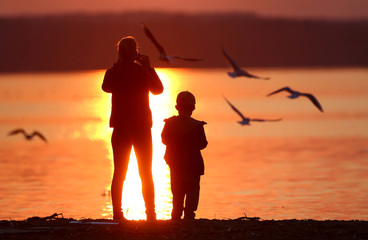 Woman takes a photo during a sunset at a lake on the outskirts of Minsk