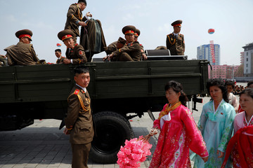 Women in traditional clothes walk past military band members getting onto a truck after a military parade marking the 105th birth anniversary of North Korea's founding father, Kim Il Sung in Pyongyang