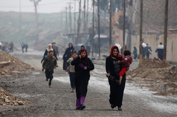 Civilians arrive to receive humanitarian aid packages in Al Ghizlane district as the battle against Islamic State's fighters continues in Mosul