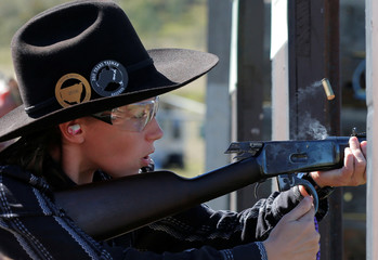 Jessica Healey, 12, under the character name 'Rosebud', sends a rifle shell flying as she re-cocks during competition at the Women of the West shooting contest at the Namoi Pistol Club in Gunnedah in rural New South Wales
