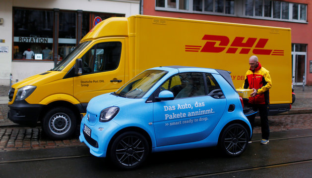 An employee of DHL poses for media in Berlin to promote a new service to deliver parcels in the trunk of smart cars