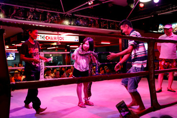 A tourist poses with a snake in a Muay Thai ring in Pattaya