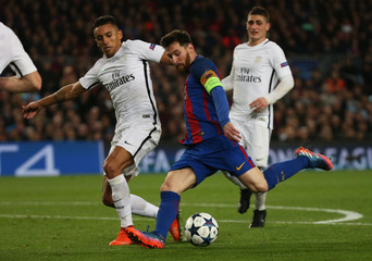 Paris Saint-Germain's Marquinhos in action with Barcelona's Lionel Messi