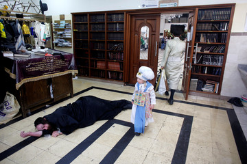 An ultra-Orthodox Jewish boy dressed in a costume walks past a drunk man lying on the floor during an annual parade marking the Jewish holiday of Purim, in Jerusalem