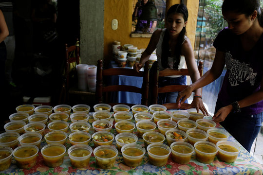 Volunteers of the Make The Difference (Haz La Diferencia) charity initiative serve cups of soup to be donated, at the home kitchen of one of the volunteers in Caracas