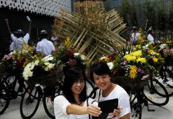 A woman takes a picture during a performance created by Japanese artist Makoto, bringing art to the streets with a fleet of 30 bicycles covered in blooms at Paulista avenue in Sao Paulo