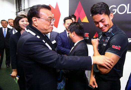 Chinese Premier Li Keqiang touches the arm of Port Adelaide player Chen Shaoliang, the Australian rules football club's international academy recruit from China, during a visit to the team's room before the start of an AFL game at the SCG in Australia