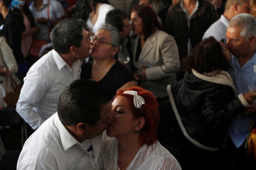 Newly-wed couples kiss during a mass wedding ceremony in which 3,400 couples participated, at Zocalo square in Mexico City