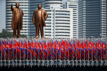 People carry flags in front of statues of North Korea founder Kim Il Sung and late leader Kim Jong Il during a military parade in Pyongyang