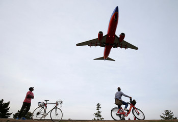 People watch airplanes land during unseasonably warm weather at Reagan National Airport in Washington