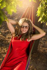 Woman in red dress lying in hammock
