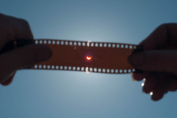 A solar Eclipse, the hand holding exposed film,