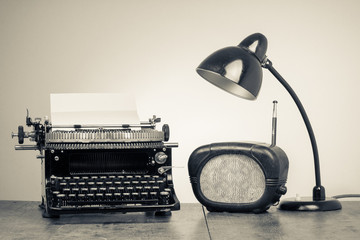 Vintage old type writer, radio and retro desk lamp on wood table