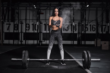Powerful, attractive muscular girl engaged in cross fit, training with barbell in the gym.