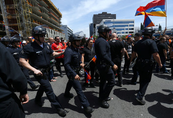 Los Angeles Police officers in riot gear head into a crowd during a march by Armenian supporters outside the Turkish Consulate in Los Angeles