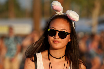 A woman walks with bunny ears in the late afternoon sun during the Coachella Valley Music and Arts Festival