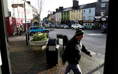 A man walks past a store in the centre of Tuam