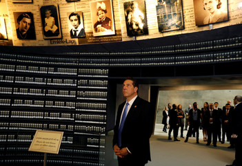 Andrew Cuomo, Governor of New York, looks at pictures of Jews killed in the Holocaust during a visit to the Hall of Names at Yad Vashem's Holocaust History Museum in Jerusalem
