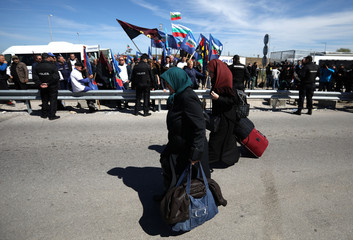 Women carry their luggage as they cross the border crossing between Turkey and Bulgaria on foot during a protest at Kapitan Andreevo border checkpoint