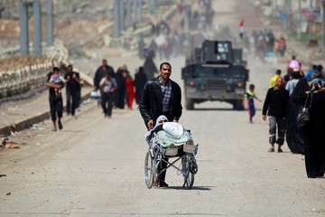 A displaced Iraqi man who fled his home pushes a woman in a wheelchair in the city of Mosul
