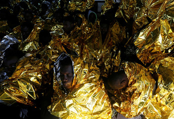 Migrants rest on the deck of the Malta-based NGO Migrant Offshore Aid Station (MOAS) ship Phoenix after being rescued from a rubber dinghy in the central Mediterranean